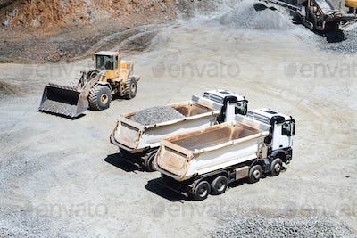 wheel loader working on site and loading dumper trucks