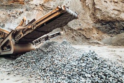 Industrial Stone breaker at ore quarry. Granite rocks crusher. Machinery, industry details