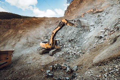 details of industrial track type excavator digging and loading ore in a dumper truck