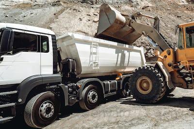 ndustrial machinery working. Wheel loader loading gravel into dumper trucks