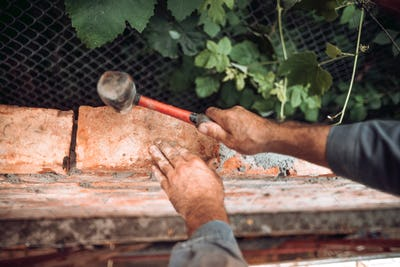 Close up of industrial worker, bricklayer installing bricks on construction site