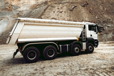 Dumper trucks unloading gravel on highway construction site