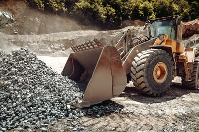 Industrial  - machinery working. Close up of wheel loader loading gravel into dumper trucks
