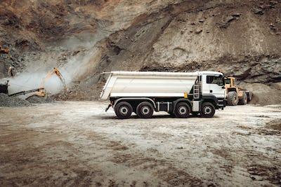 Industrial dumper trucks working on highway construction site