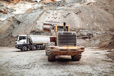 Wheel loader bulldozer with blade loading dumper trucks on construction site