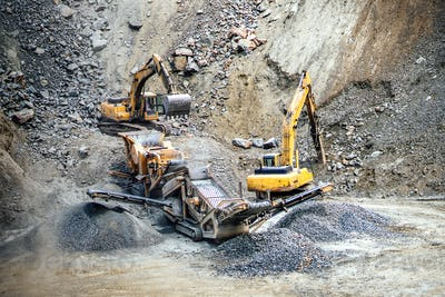 Industrial machinery and heavy duty excavators working at rock quarry