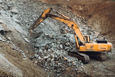 Industrial track type excavator digging at a quarry or a construction site, machinery details