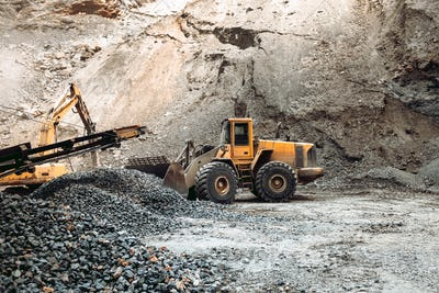 Industrial machinery on ore quarry site, heavy duty excavator moving gravel and rocks.