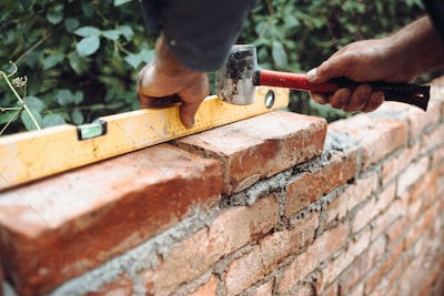 professional construction worker laying bricks and building brick walls in industrial site