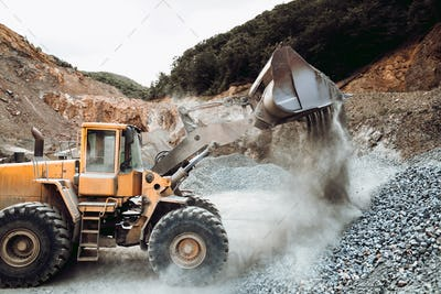 Industrial heavy duty wheel loader moving gravel on construction site