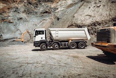 Wheel loader loading gravel into dumper trucks. Industry details - machinery working.