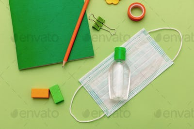 Medical protective mask, hand sanitizer gel and school supplies on pastel green color background