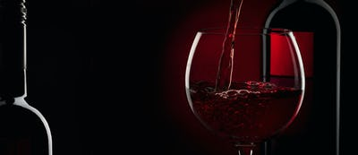 Pouring red wine into the glass against red black background. Panoramic banner