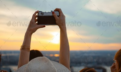 Young girl taking sunset photo on the roof