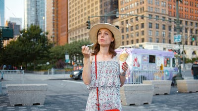 Attractive girl eating ice cream outdoors