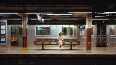 Young woman waiting for a train at the station in the subway