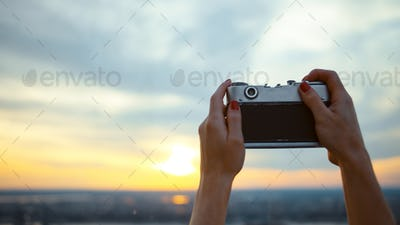 Young girl taking sunset photo in NYC