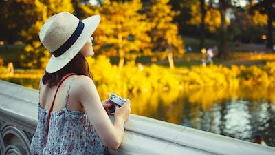 Beautiful girl with a retro camera in Central Park