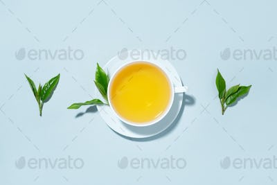 Green tea brewed in white cup on blue background
