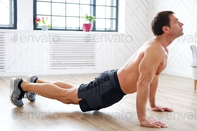 A man doing stomach workouts on the floor.