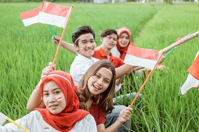 Asian youth smiles holding small red and white flags sitting in the middle of rice fields