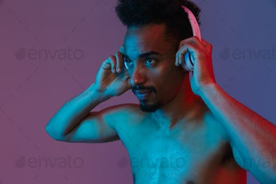 Portrait of unshaven shirtless african american man poising with headphones