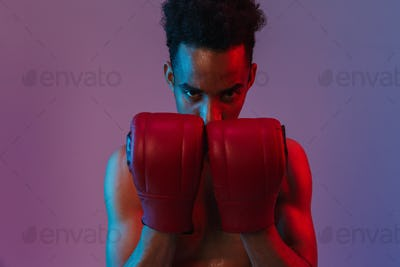 Portrait of aggressive shirtless african american sportsman poising in boxing gloves