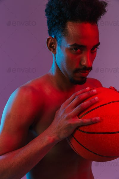 Portrait of young sporting shirtless african american man poising with basketball