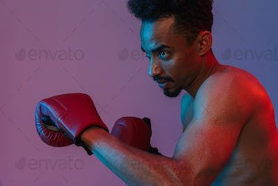 Portrait of concentrated half-naked african american man poising in boxing gloves