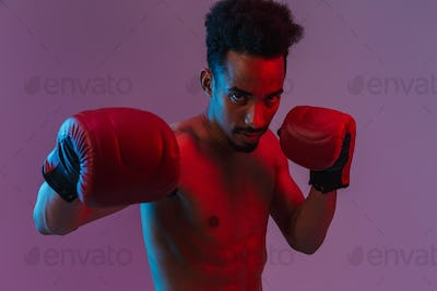 Portrait of handsome half-naked african american man poising in boxing gloves