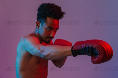 Portrait of masculine half-naked african american man poising in boxing gloves