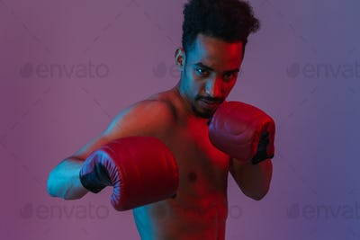 Portrait of focused half-naked african american man poising in boxing gloves