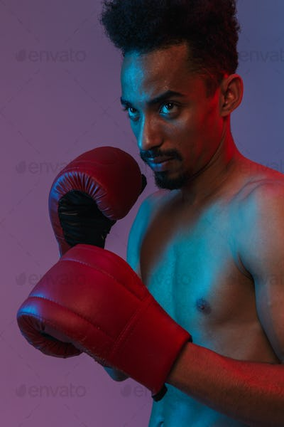 Portrait of half-naked african american sportsman poising in boxing gloves