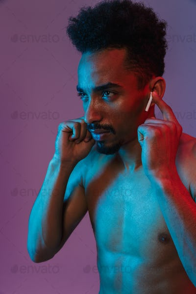 Portrait of bearded shirtless african american man poising with earpod
