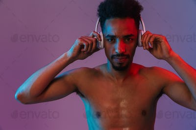 Portrait of shirtless african american man poising with headphones and looking at camera