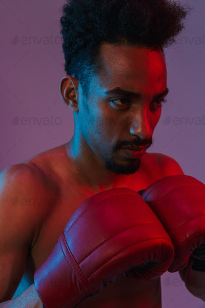 Portrait of young shirtless african american sportsman poising in boxing gloves