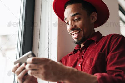 Happy young man near window using mobile phone