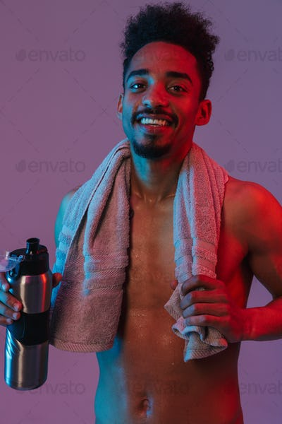Portrait of laughing shirtless african american man poising with thermos bottle and towel