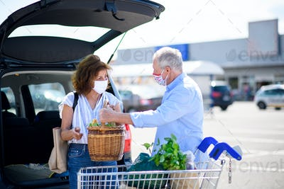 Senior couple with face masks putting shopping in car outside supermarket in city