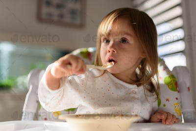 Two years old eats brakefast by herself with a spoon