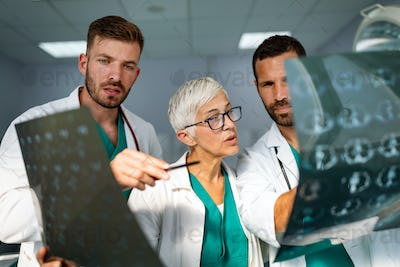 Doctors discussing patient's diagnosis looking at x-rays in a hospital