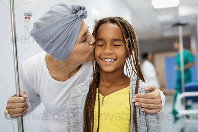 Sick woman with cancer hugging her young grandchild in hospital. Family support concept