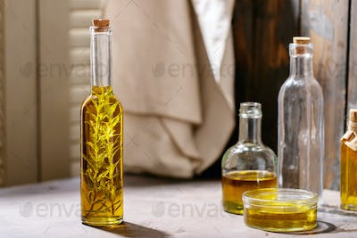 Olive oil with rosemary in glass bottles