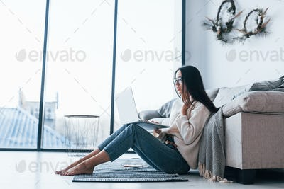 Young beautiful woman in glasses sitting at home alone with laptop