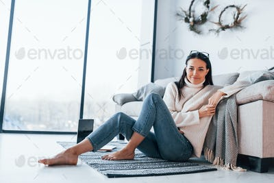 Young beautiful woman in casual clothes sitting at home alone