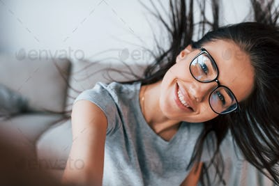 Making selfie. Young beautiful woman in casual clothes and glasses have fun at home alone
