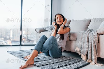 Woman in casual clothes sitting at home alone and listening to the music in headphones