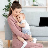 Mother-baby emotional attachment. Loving mom hugging her adorable toddler son at home