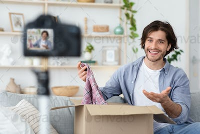 Cheerful man broadcasting from home, showing his purchases
