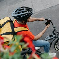 Bicycle courier in protective helmet with delivery backpack sits on bicycle and looks at phone and
